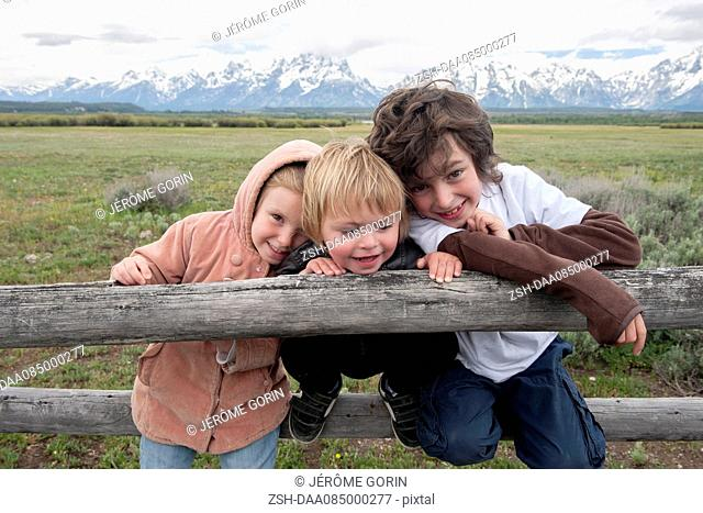 Children leaning against fence in Grand Teton National Park, Wyoming, USA