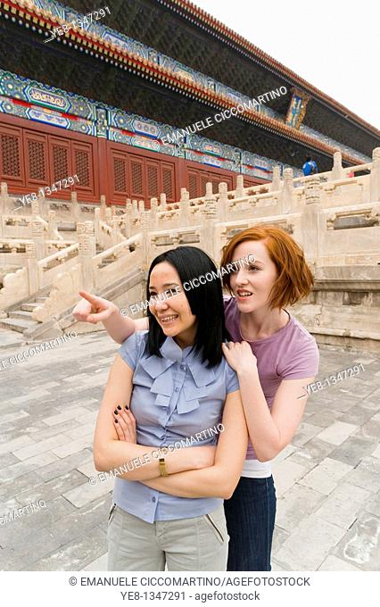 Tourist pointing something out to her friend in The Forbidden City, Beijing, China, Asia  MR