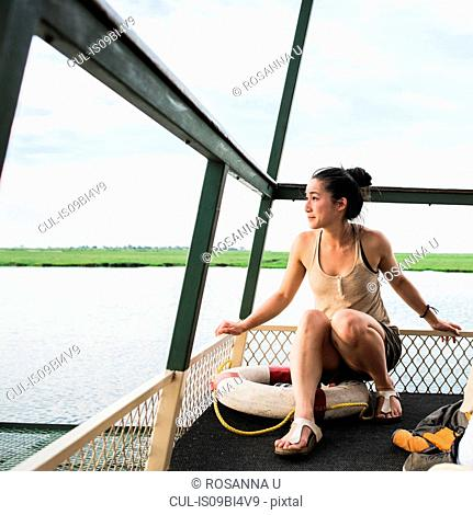 Young female tourist on Chobe River tour boat, Botswana, Africa