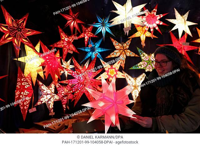 Christmas stars glow at a stand at the Nuremberg Christmas market in Nuremberg, Germany, 01 December 2017. Photo: Daniel Karmann/dpa