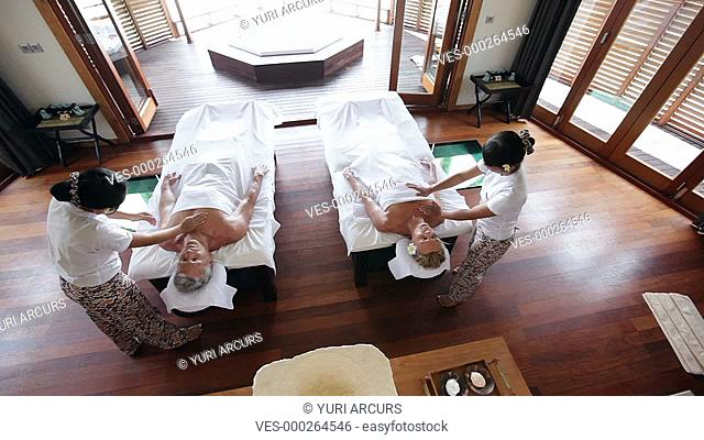 Top view of a mature couple receiving simultaneous massages at a luxury resort