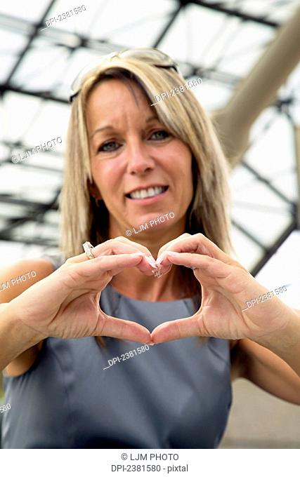 Mature Professional Business woman Making An I Love You Sign With Her Hands By Forming A Heart Shape; Edmonton, Alberta, Canada