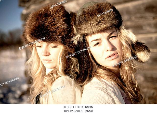 Portrait Of Two Girls Standing By A Log Cabin Wearing Fur Hats; Homer, Alaska, United States Of America