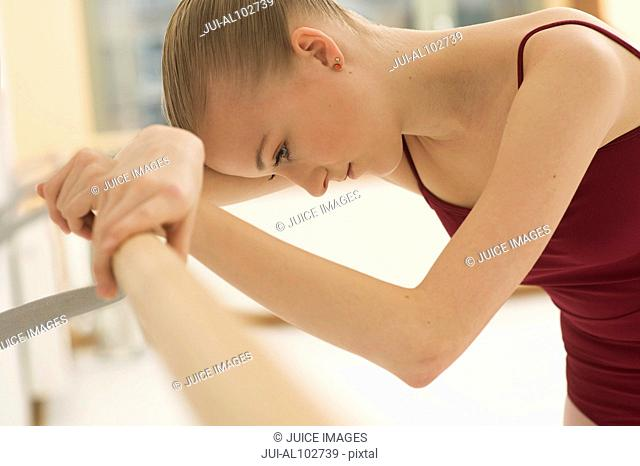 A ballet dancer leaning on the barre looking down