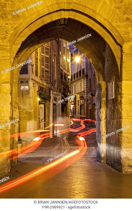 Car light-trails through entry gate to Place de l'Hotel de Ville at night, Aix-en-Provence, France