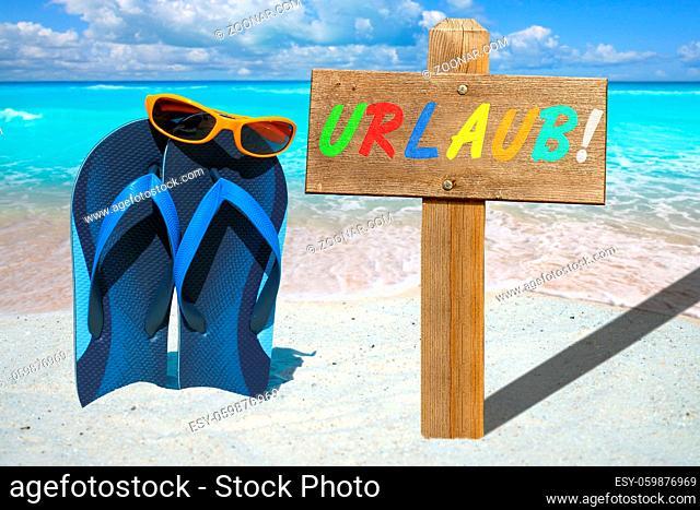 Flip Flops, Sonnenbrille und Holzschild mit Text URLAUB