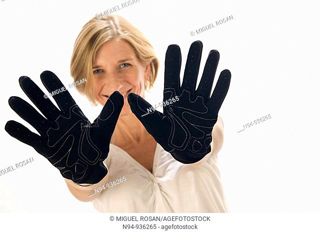 Young blonde girl showing the palms of the hands in black gloves