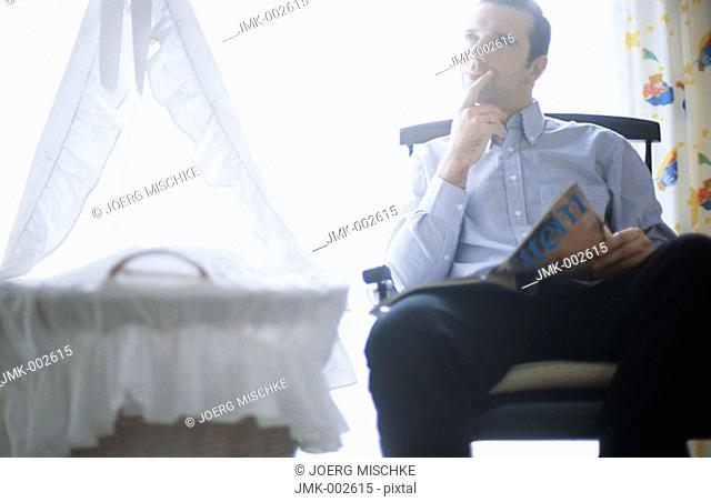 A young man, 25-30 30-35 35-40 years old, sitting in a rocking chair in the nursery, next to the cradle, reading