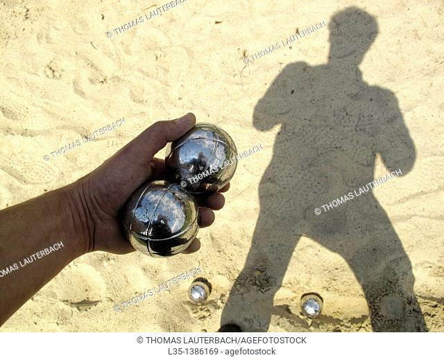 A man holding two bocce balls in his hand, his shadow in the background