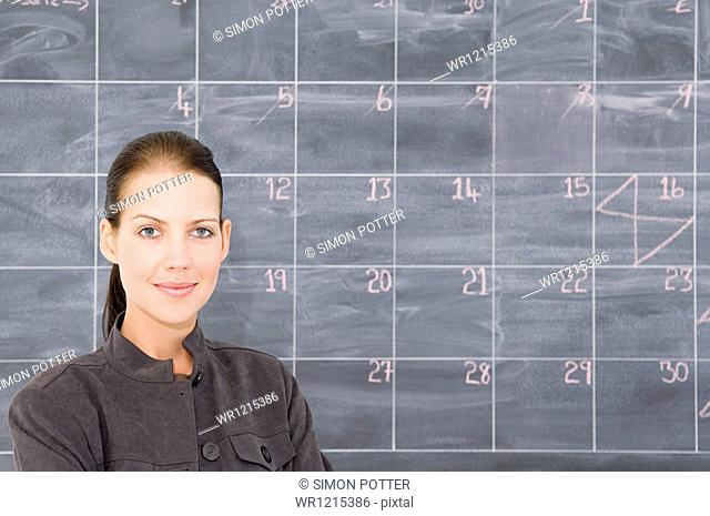A young woman in front of a blackboard marked out as a calendar