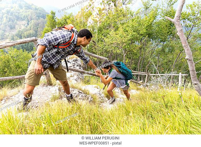 Italy, Massa, man helping a young woman to climb a step while hiking in the Alpi Apuane mountains