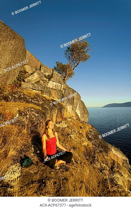 A young woman meditates along the bluffs of Stillwater, near Powell River. Stillwater Bluffs, The Sunshine Coast, ,British Columbia, Canada