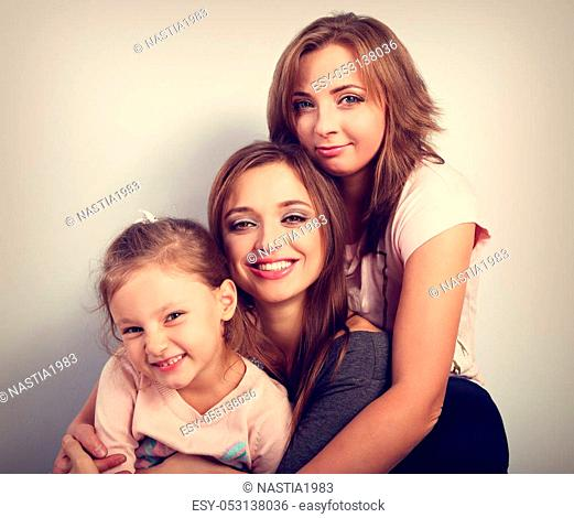 Two young beautiful smiling women and happy joying kid girl hugging with love. Toned closeup portrait