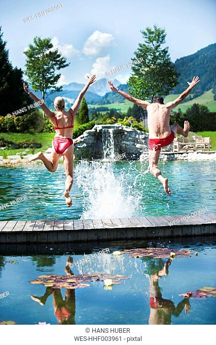 Austria, Salzburg County, Couple jumping into swimming pool