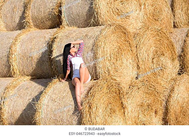 Beautiful young woman with sunglasses and black long hair in white shorts and plaid shirt sitting on bale of straw in the field and enjoying on sun