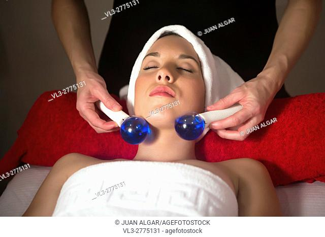 Brunette with eyes closed in spa getting face massage