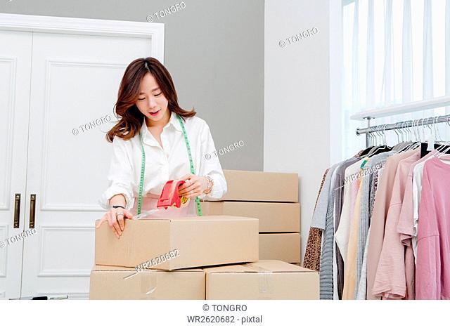 Female fashion designer making packages