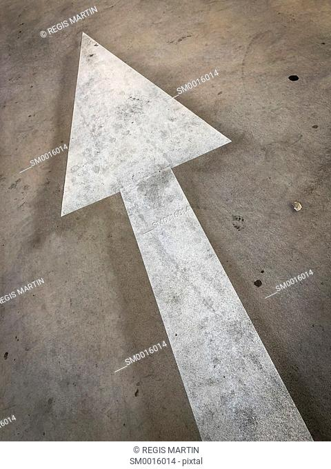 Painted white arrow indicating a direction on a concrete floor