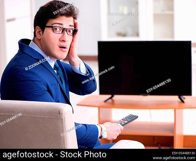 The businessman watching tv in the office
