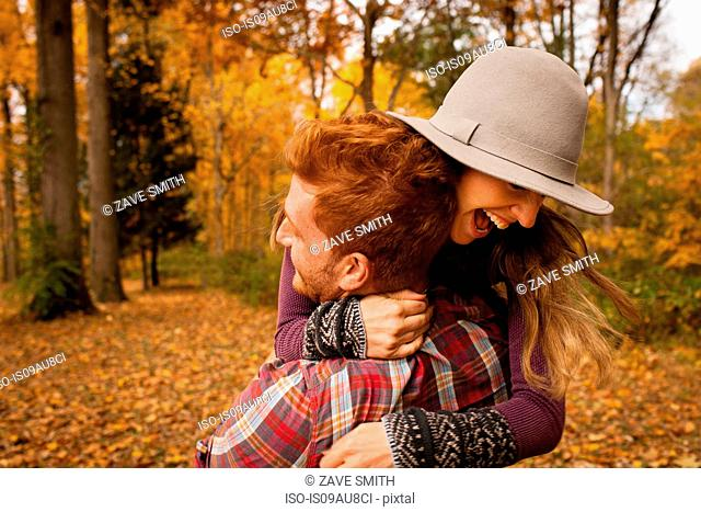 Young couple hugging in autumn forest