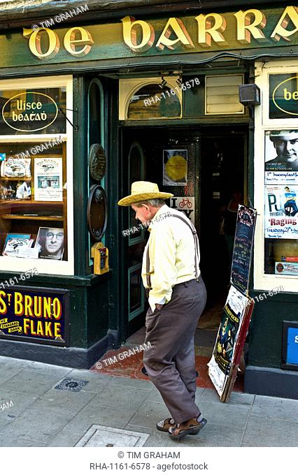 Man walking past de Barra bar in Timoleague, West Cork, Ireland