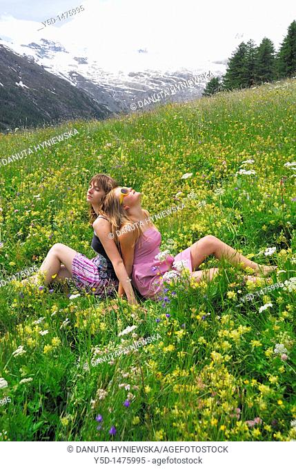 Two young women sitting, arm in arm, in flowers, mountains, Saas Fee, Swiss Alps, Switzerland