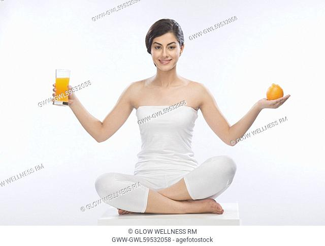 Woman holding an orange and a glass of orange juice
