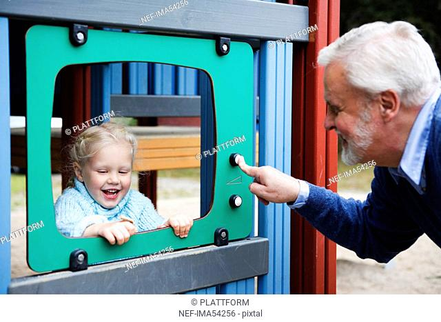 Grandfather and grandchild playing together on a playground, Sweden