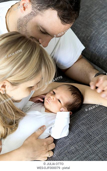Young couple with newborn baby boy at home