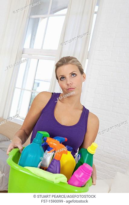 Tired young woman holding cleaning products
