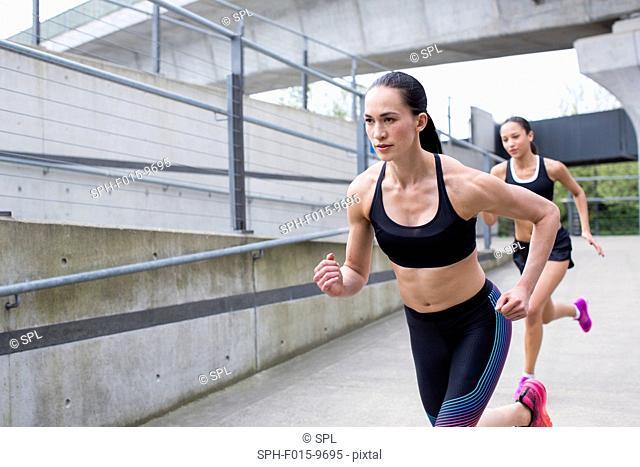 MODEL RELEASED. Two young women running in urban scene