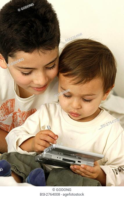 Brothers playing to a video game Nintendo DS
