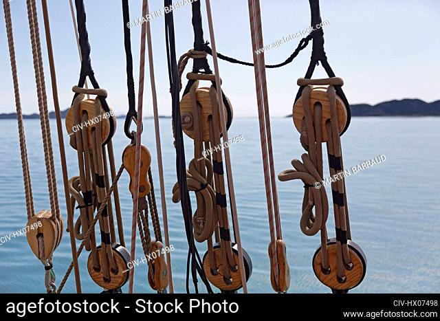 Wooden sailboat pulleys and rigging on ocean