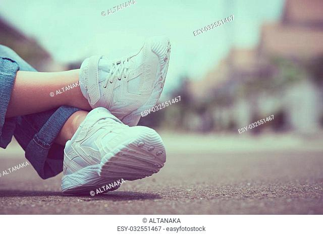 youth sneakers on girl legs on road during sunny summer day