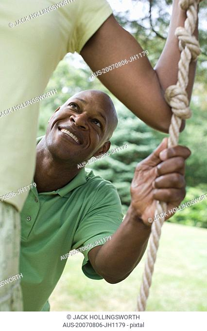 Mid section view of a mid adult woman standing on a rope swing with a mature man pushing her