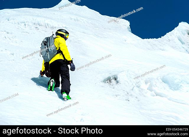 A skier in a helmet and mask with a backpack rises on a slope against the background of snow and a glacier. Backcountry Freeride
