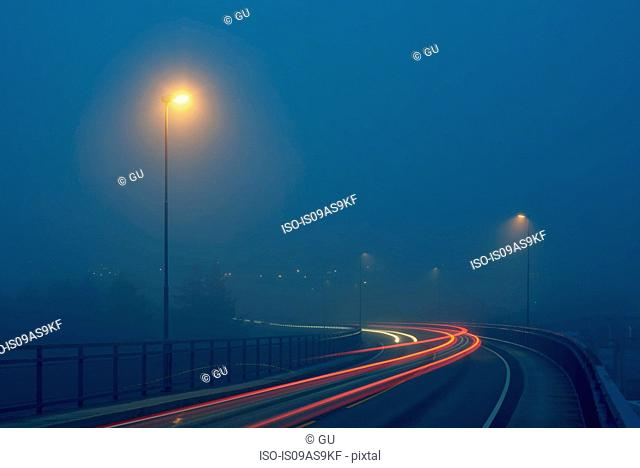 Diminishing perspective of light trails on misty road illuminated by street lights, Haugesund, Rogaland County, Norway