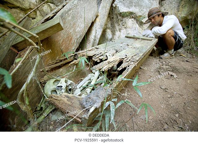 a male tourist examines an old coffin with the skeletal human remains intact, that was once hanging high on a cliff, near mountain village of sagada