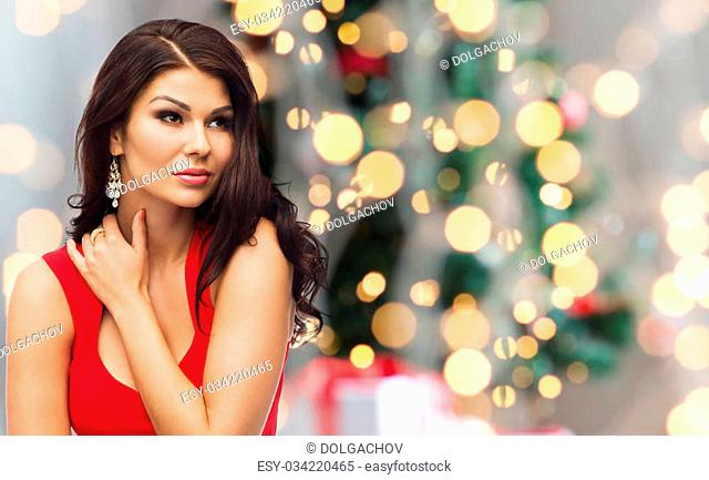 people, christmas, holidays and luxury concept - beautiful sexy woman in red dress over lights background