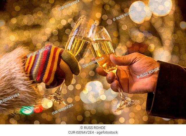 Close up of couples hands making a champagne toast in front of xmas lights