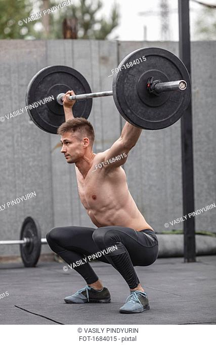 Shirtless male athlete lifting barbell during crossfit training