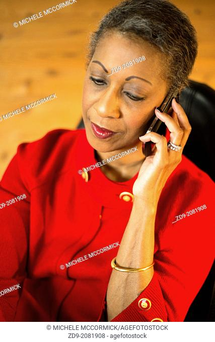 An attractive middle-aged professional black woman talks on her cell phone