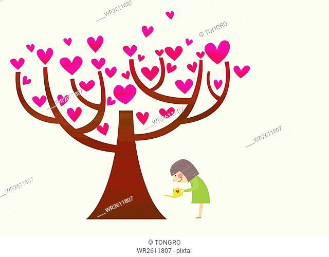 Woman watering a heart tree