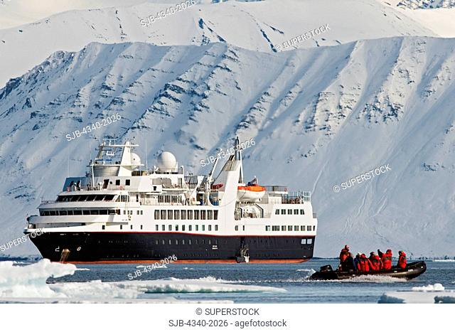 Zodiacs filled with tourists disembark from a cruise ship to view a polar bear sow and cub resting on Andoyane island, Liefdefjorden, northwest Svalbard, Norway