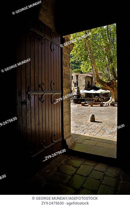 The village square seen through the abbey doorway, St Guilhem le Desert, Languedoc-Roussillon, France