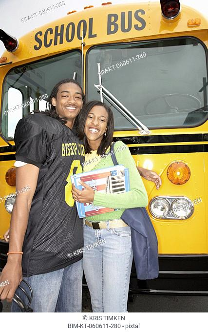Young African man in football uniform with girlfriend next to school bus