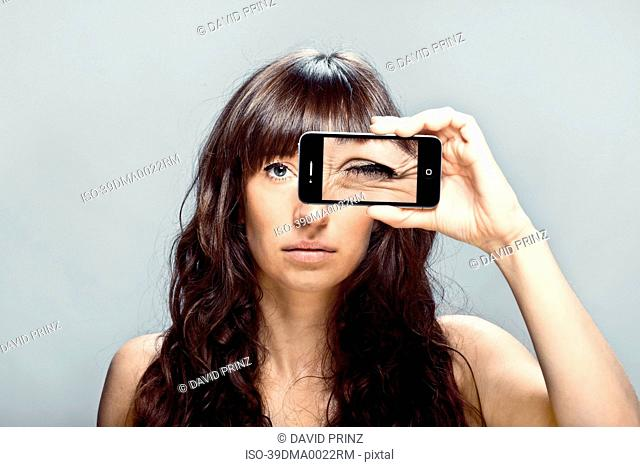 Woman with cell phone picture of eye