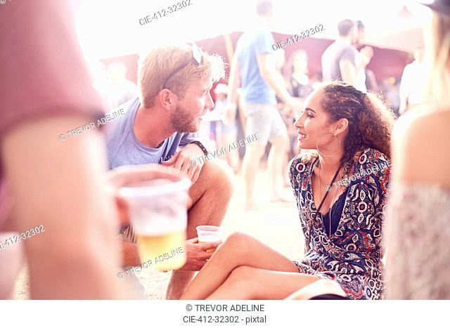 Young couple drinking beer and talking at music festival