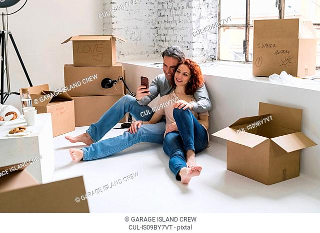 Couple moving into industrial style apartment, sitting on floor looking at smartphone