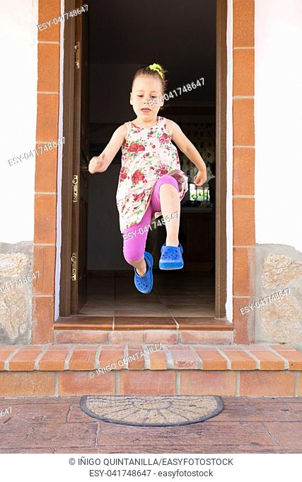 front view of four years old blonde girl with dress and pigtail jumping, or taking a great leap, from the exterior doorway of the house